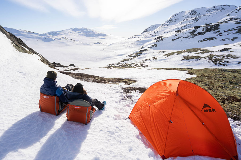 sitting in camp chairs by winter tent