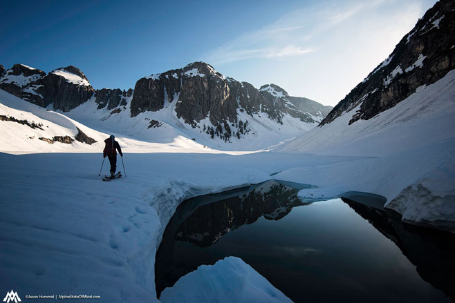 Tim Black skinning across Upper Berdeen Lake, deep in North Cascades National Park.