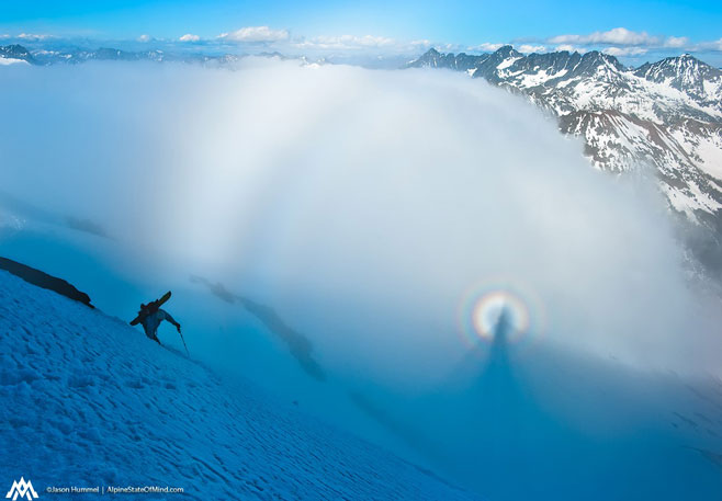 After a few days in the clouds on the American Alps Traverse, Kyle Miller climbs up the final slopes of Fortress Mountain while a Brocken Spectre blossoms in the clouds below.