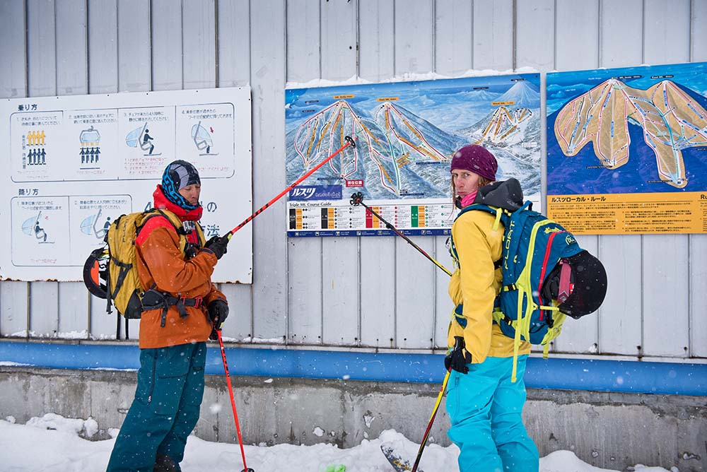 Adam U and Tess Golling inspect the trail map at the bottom of a closed lift.