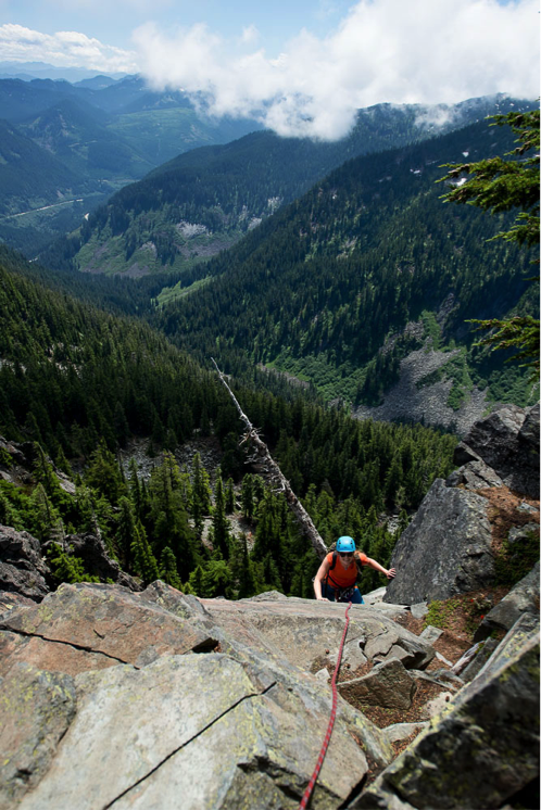 Justus topping out on the first pitch in good spirits, despite apparently being impaled by a sizeable dead snag. You can see Interstate 90 way down below.