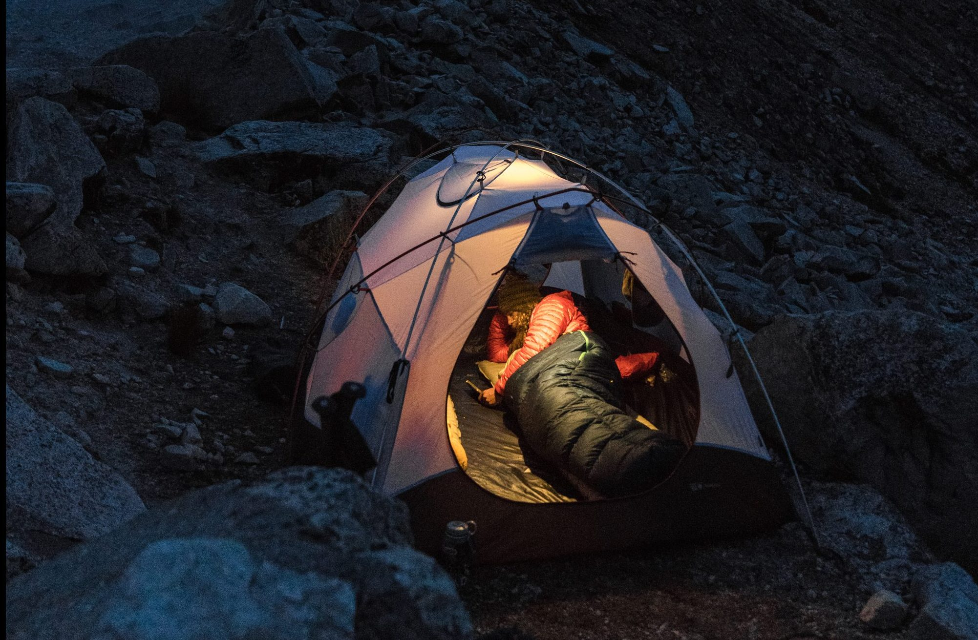 camper in tent in sleeping bag at night