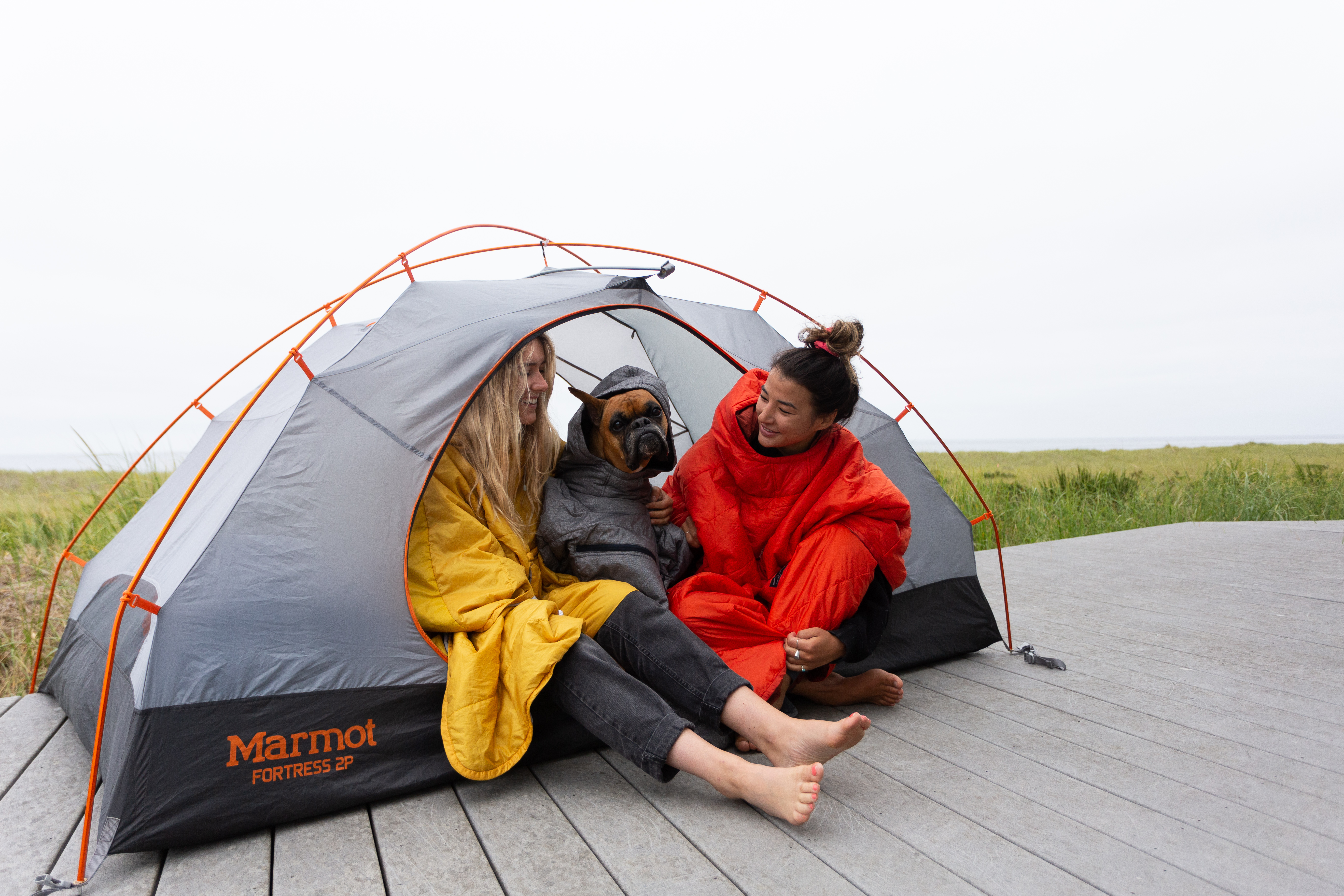 2 girls in a tent wearing ponchos with a dog
