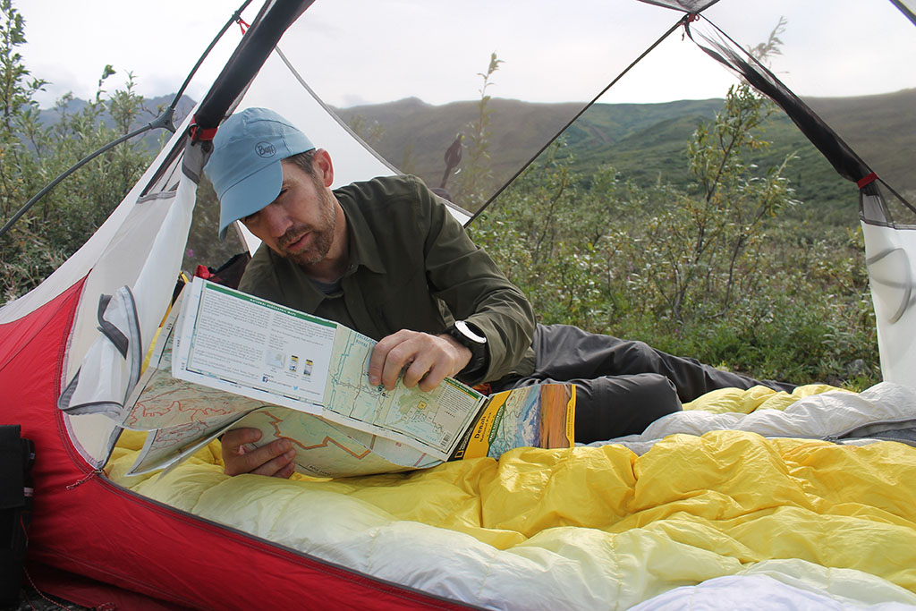 looking at map in tent on sleeping bag