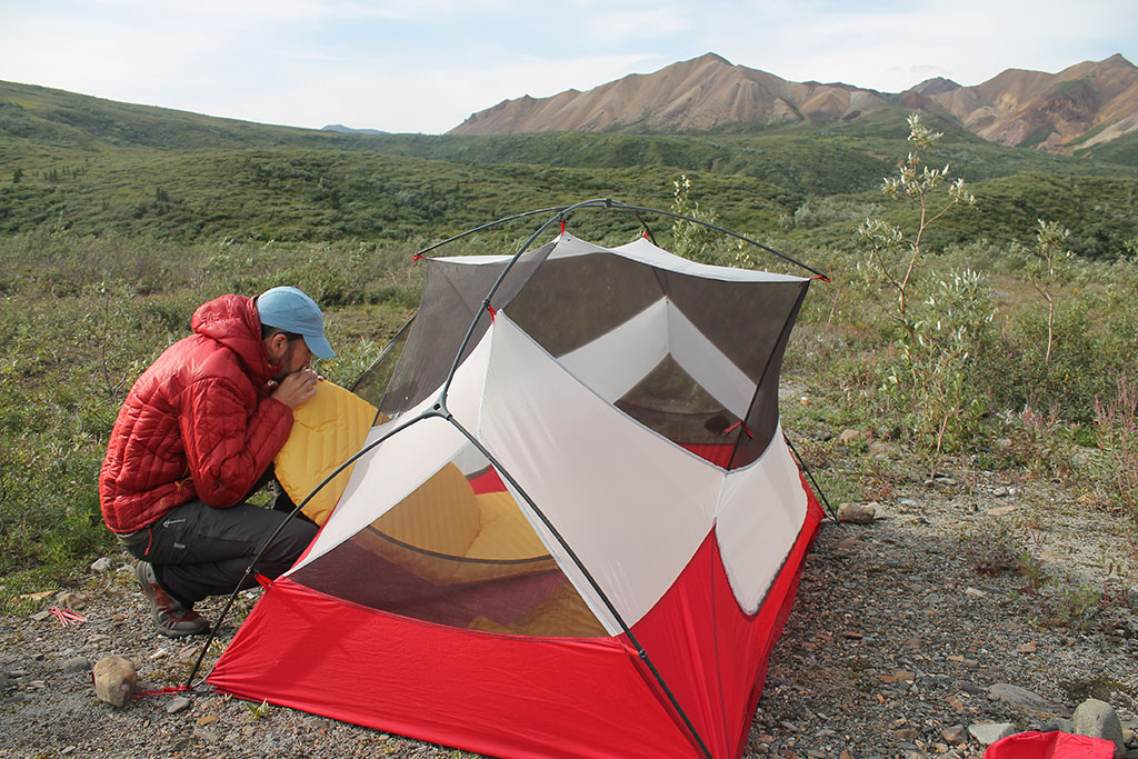 inflating sleeping pad in tent at sustainable campsite