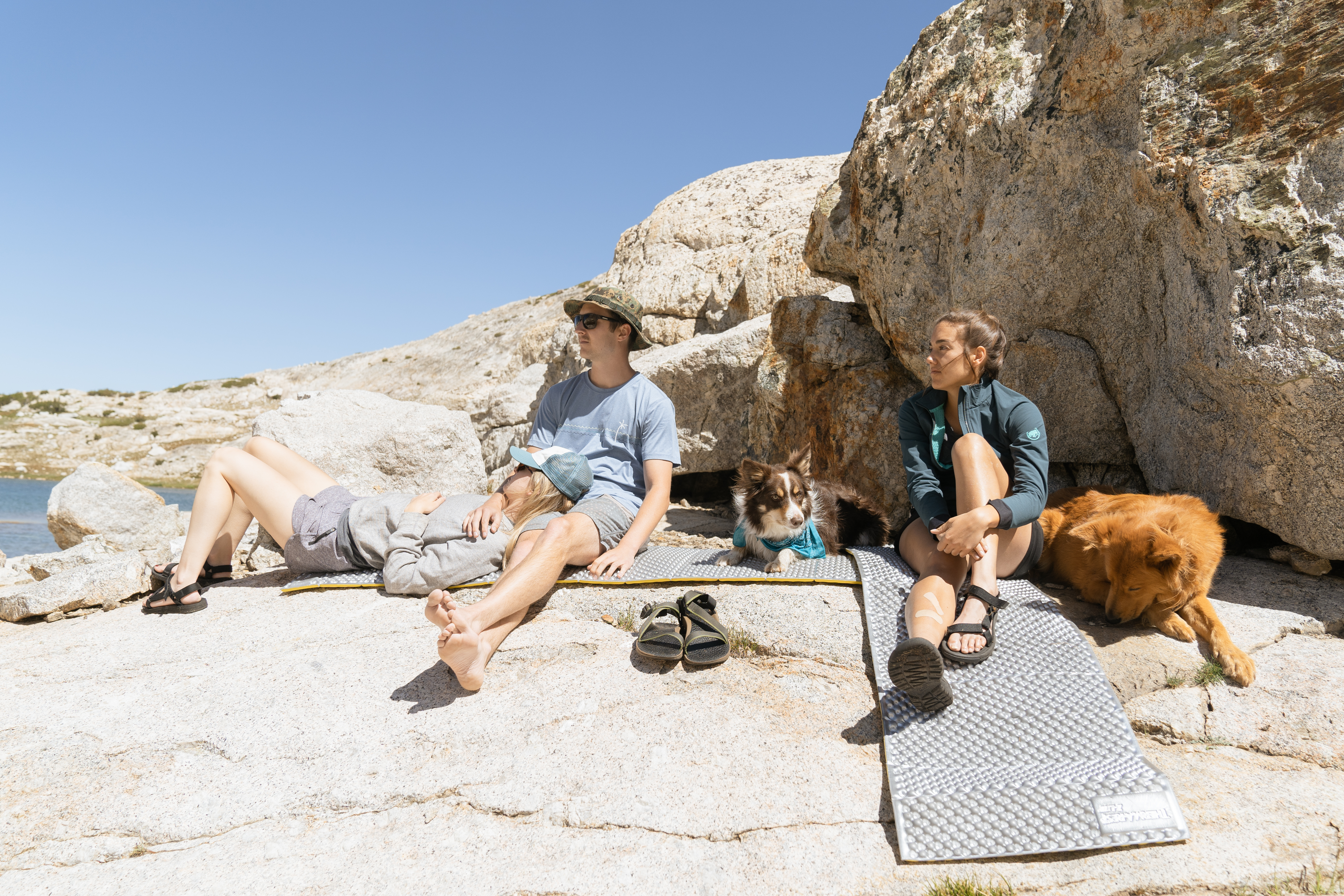intro to backpacking group sitting on sleeping pads with dogs