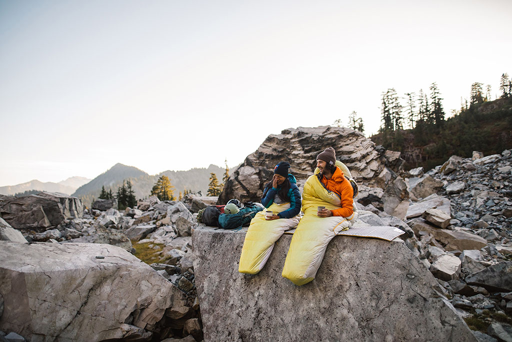 man and women in sleeping bags sitting on boulder