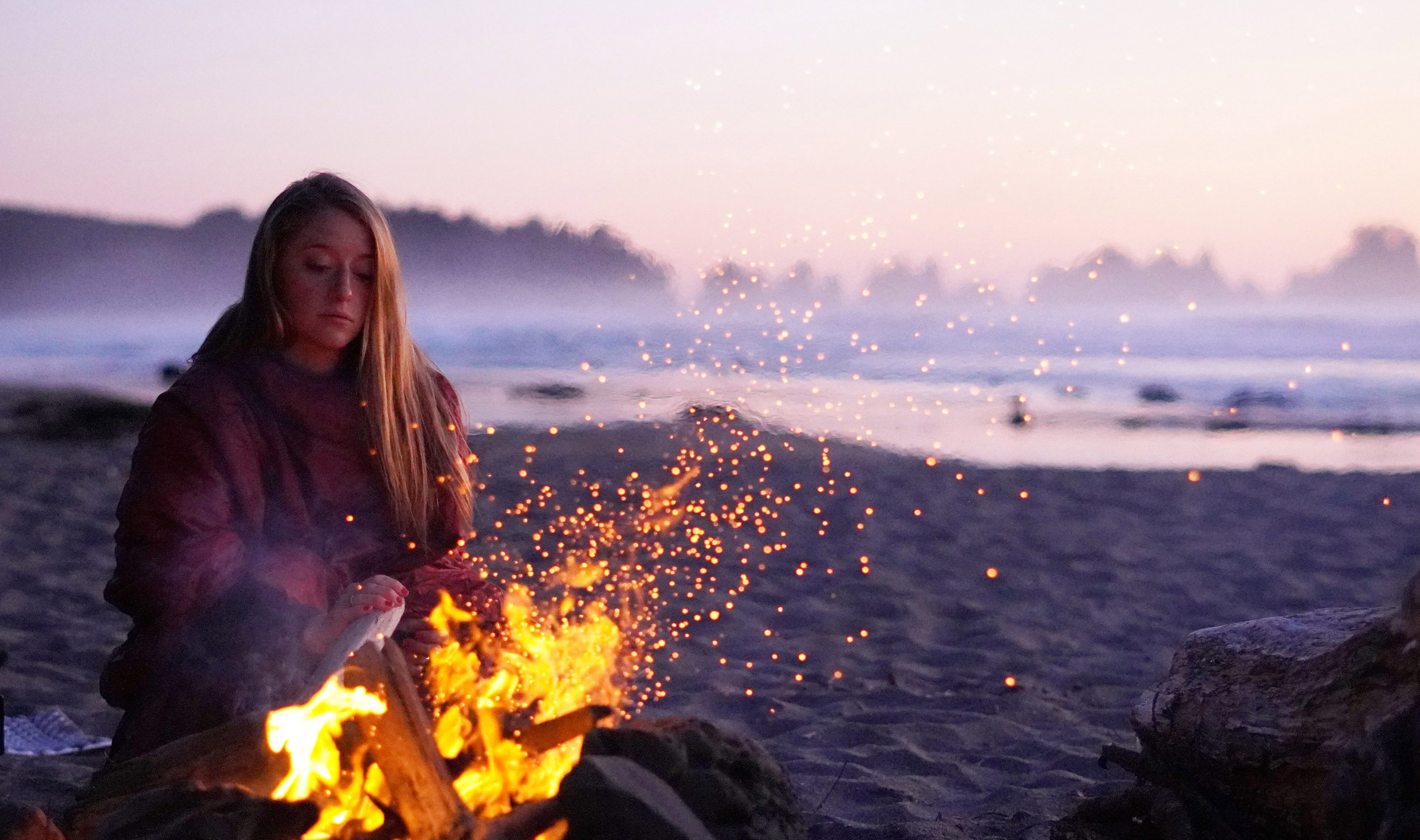 woman at campfire on the beach