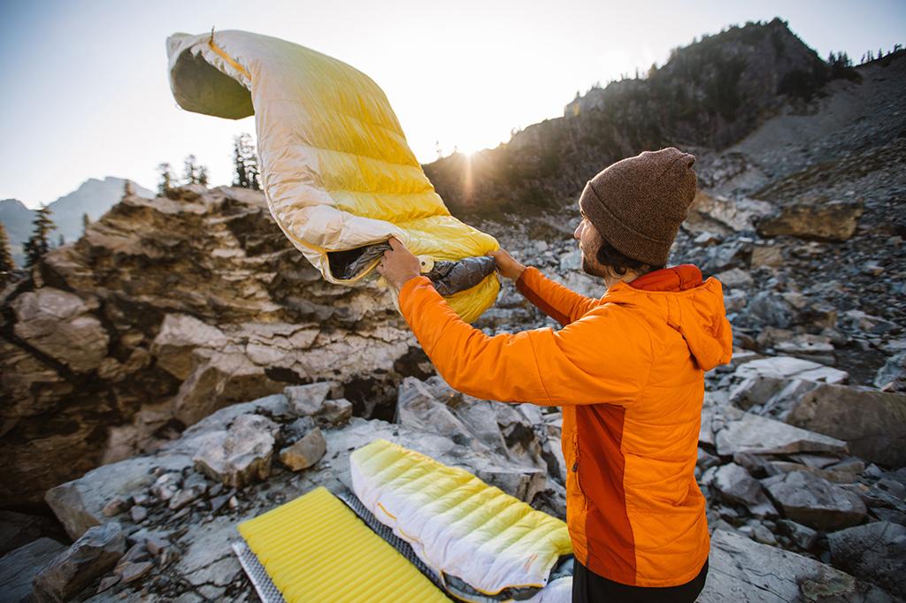 setting up sleeping bag at campsite