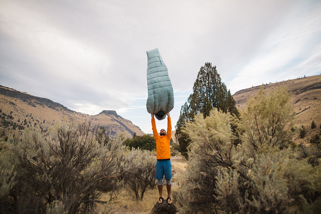 shaking out sleeping bag in warm weather