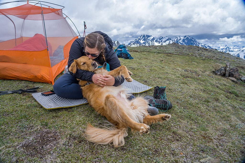 sitting on sleeping pad with dog