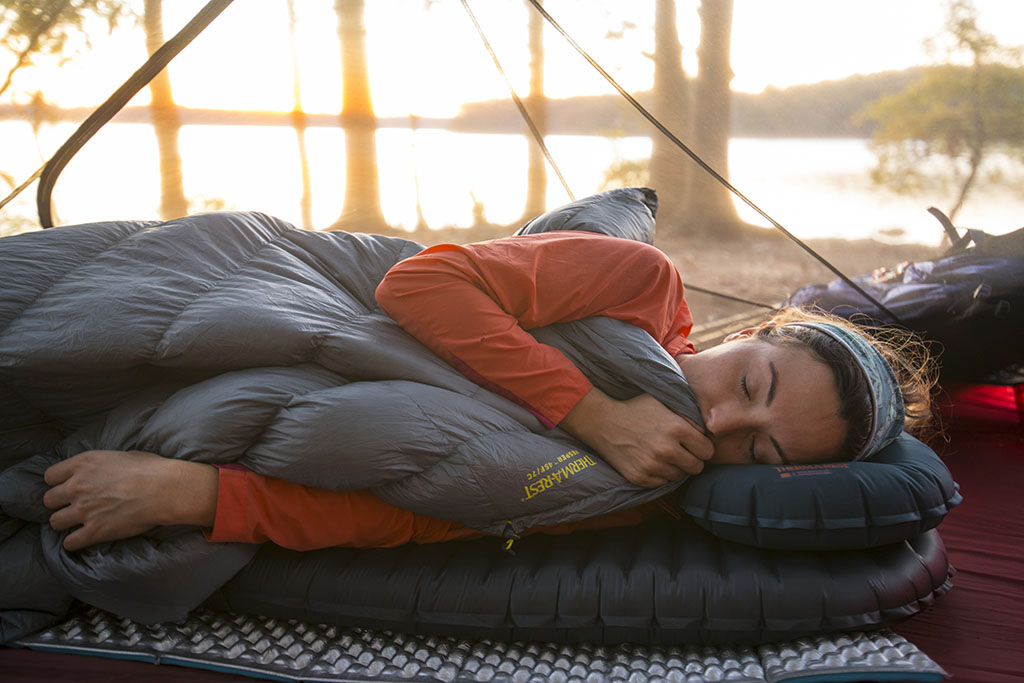 sleeping with a camping quilt and camping pillows on sleeping pads