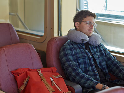 Person sleeping on a train using the Neck Pillow